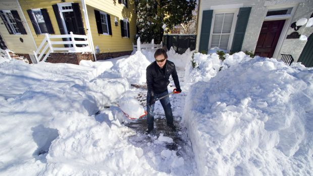 Maok Niebaur, 25, shovels snow for an elderly neighbour in Alexandria, Virginia on Sunday. Millions of Americans are ...