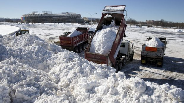 Snow from around the Washington area is dumped in the parking lot of Robert F. Kennedy Memorial Stadium in Washington.