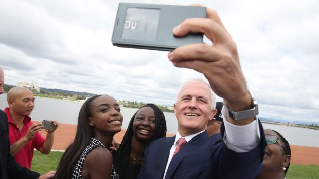 Prime Minister Malcolm Turnbull takes a selfie with new Australian citizens Lydia Banda-Mukuka and Chilandu Kalobi ...