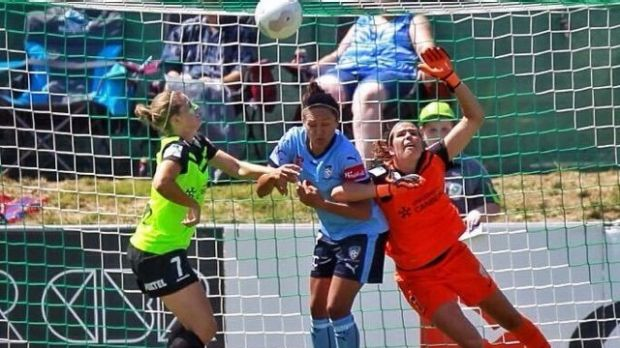 Game-changer: Canberra United goalkeeper Lydia Williams is obstructed by Sydney FC striker Kyah Simon.
