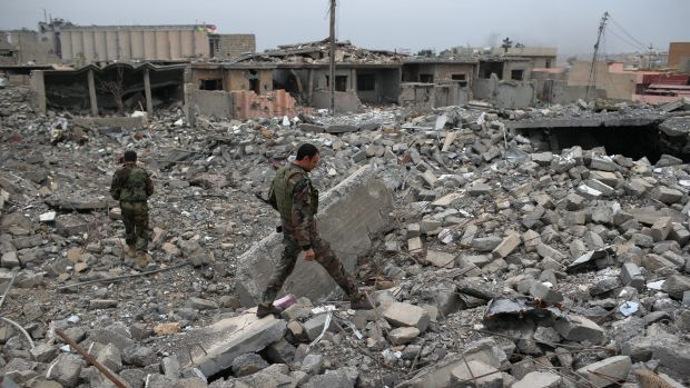 Kurdish Peshmerga soldiers - allies with the PKK - search for weapons in the rubble of a US-assisted airstrike in ...