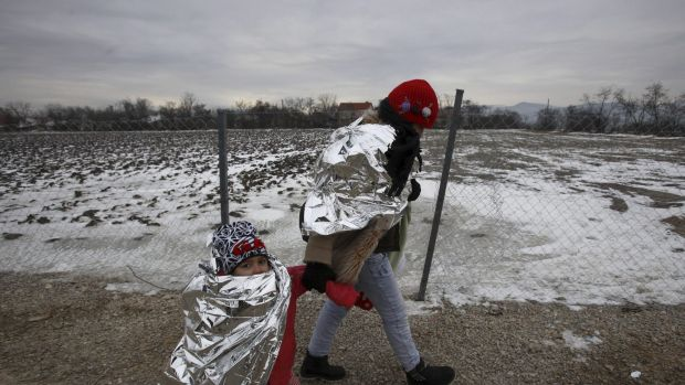 A refugee woman and a child walk in freezing weather towards the border with Serbia from a transit centre for refugees ...