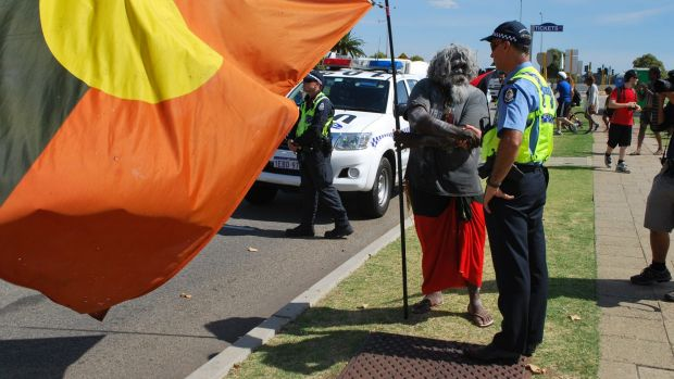 A police officer greeting Nyoongar man Herbert Bropho during a peaceful protest on Australia Day.