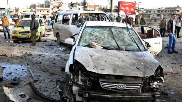 Syrian citizens gather around cars destroyed by the Islamic State bombs.