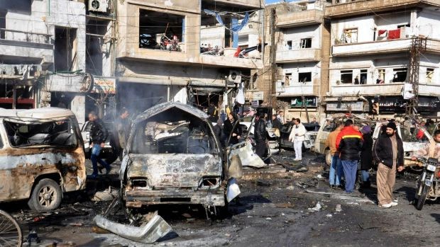 Syrian citizens gather at the scene where twin bombs exploded at a government-run security checkpoint in the Homs ...