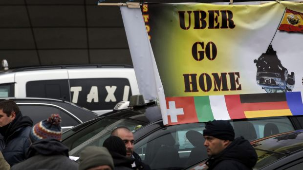 Taxi drivers on strike stand next to their cars as they demonstrate in Paris.