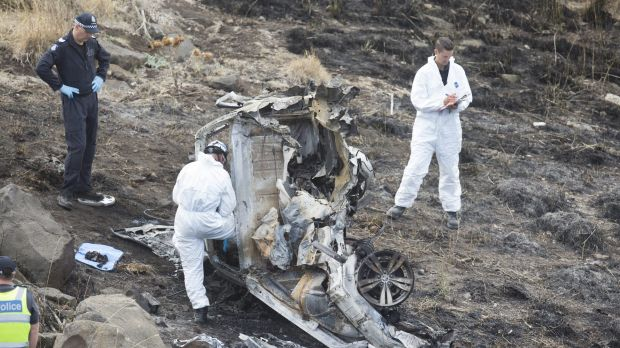 Police investigators pick over the wreckage of the car, which crashed 50 metres off the EJ Whitten Bridge in Melbourne ...