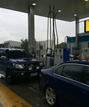 Customers queue for free fuel at Metro petrol station in Fyshwick at noon.