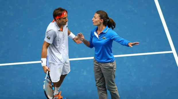David Ferrer talks with the chair umpire before a break in play while the roof on Rod Laver Arena closes as storms hit ...