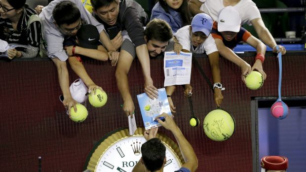 Fan favourite: Milos Raonic signs autographs after the match.
