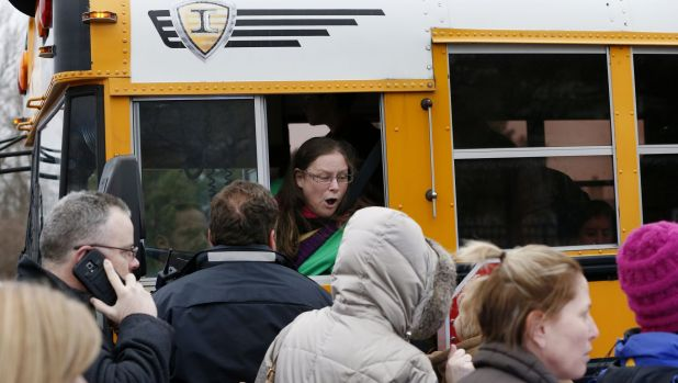 A school bus driver yells to a parent that their child is safe after a bus accident at Amy Beverland Elementary School ...