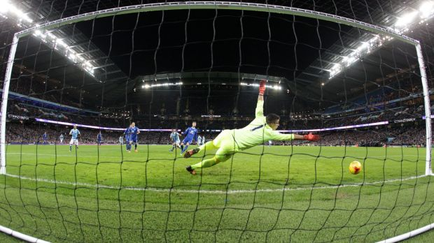 Manchester City's Sergio Aguero (left) scores his side's third goal past Everton's goalkeeper Joel Robles.