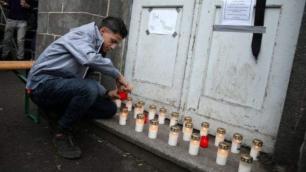 A young man lights a candle at a makeshift memorial to a young Syrian man believed to have died while waiting to receive ...