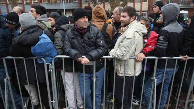 Asylum applicants wait outside the Central Registration Office for Asylum Seekers (LAGeSo) to receive their benefits the ...