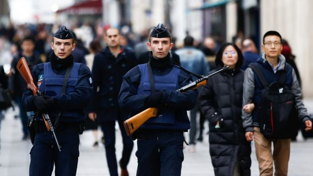 Pedestrians walk alongside police officers  in the Champs Elysees in Paris, the day after the November 13 terrorist attacks.
