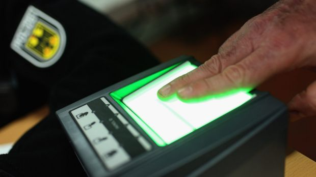 A migrant gives his finger print at a processing centre in Passau, Germany. German police only allow migrants to enter ...