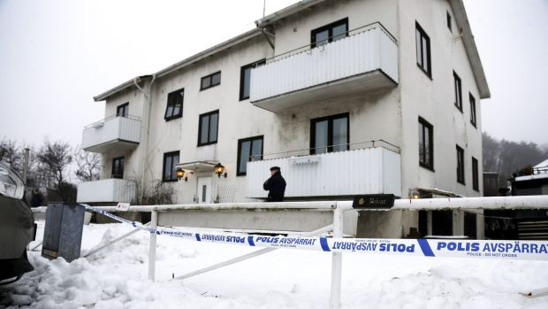 A police officer stands guard at the entrance of a migrant centre in Molndal outside Gothenburg, Sweden, on Monday. ...