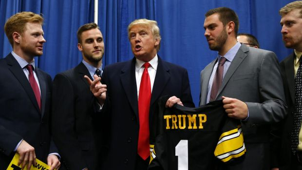 Republican presidential candidate Donald Trump speaks with University of Iowa football players before a campaign event ...