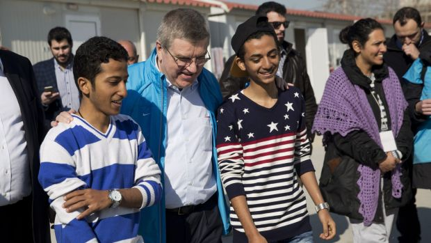 IOC President Thomas Bach (second left) chats with two young refugees during his visit at a refugee camp in Athens.