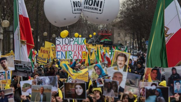 "A demonstrator holds up a sign reading ""Stop Executions in Iran"" as Iranian opposition protesters march in Paris during ..."