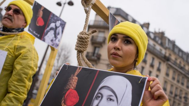 Demonstrators pose with a symbolic rope around their necks as Iranian opposition protesters march during a rally against ...