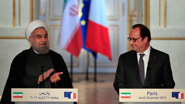 Iranian President Hassan Rouhani, left, applaudes France's President Francois Hollande, at a press conference at the ...
