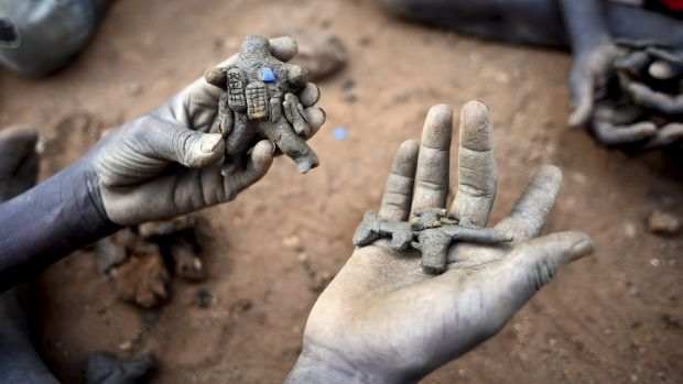 A displaced child holds clay toys of a peacekeeper and a rifle, in the UN camp for displaced people in the capital Juba, ...