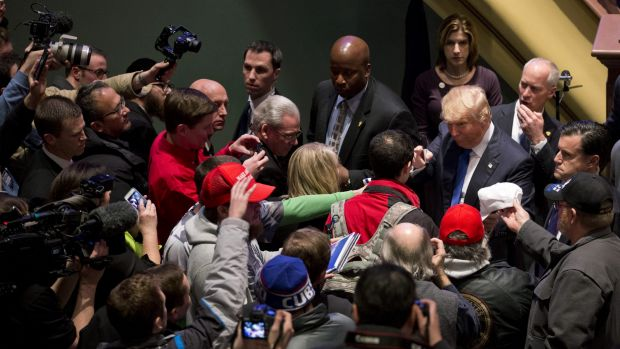 Republican presidential candidate Donald Trump, far right, signs autographs after a campaign event on the campus of ...