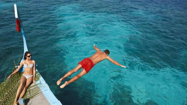 A tourist takes a dive from a dhoni boat.