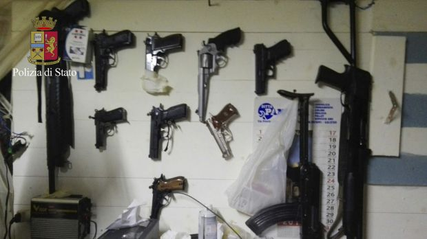 In this photo released by the Italian Police, weapons hang on a wall of the hidden bunker where 'Ndrangheta clan bosses ...