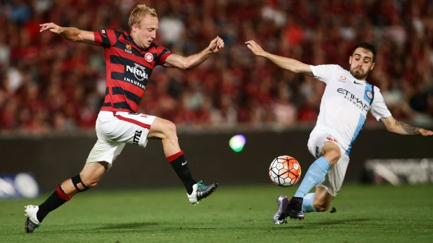 Attack: Mitch Nichols of the Wanderers and City's  Anthony Caceres battle for the ball.