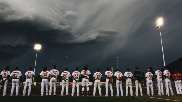 Canberra Cavalry players line up during a moment of respite from the weather.