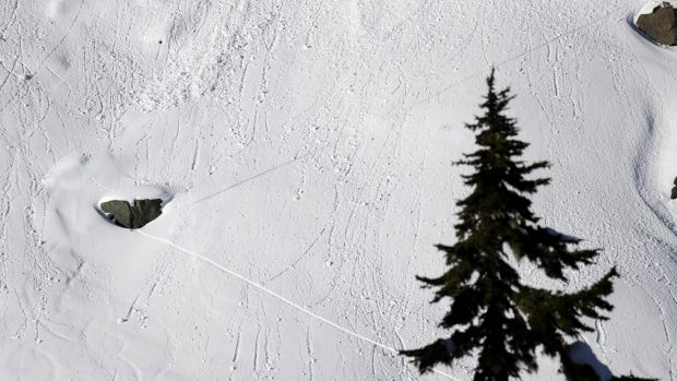 "In this January 11 photo, a pair of diagonal lines left by a skier cross dozens of lines left by ""roller balls,"" are a ..."