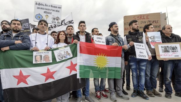 Protesters hold posters and flags during a demonstration against the Syrian regime during Syrian Peace talks in Geneva, ...