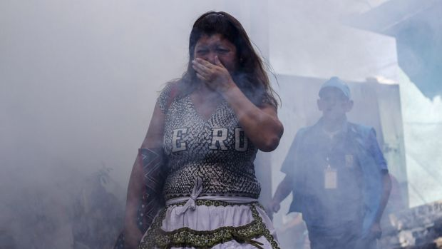 A woman covers her mouth while city workers fumigate insecticide to help combat the Aedes Aegypti mosquitoes that ...