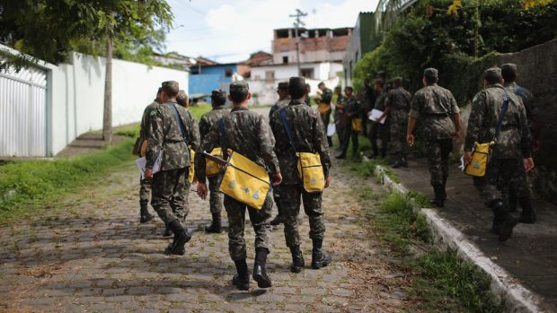Brazilian soldiers canvass a neighbourhood to tell residents to prevent mosquito bites.