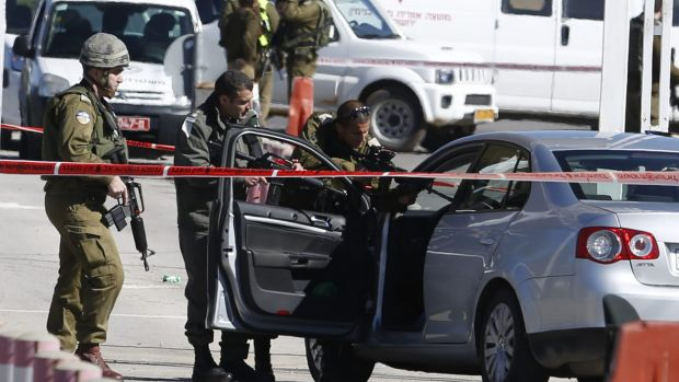 Israeli security forces at the checkpoint between the city of Ramallah and Jewish settlement of Beit El in the West Bank ...