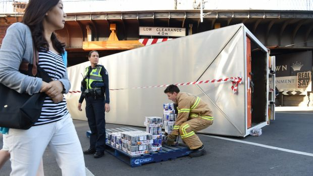 Red Bull rollover. Emergency services remove the freight from the truck that rolled over at the Flinders Street Bridge.