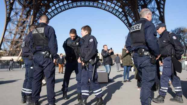 French police officers stand guard at the Eiffel Tower in Paris, France.