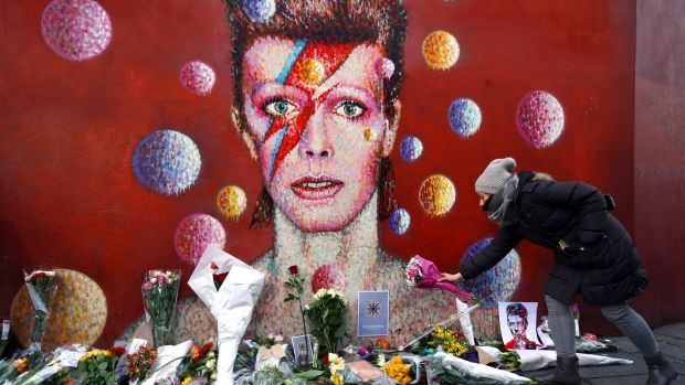 A woman leaves flowers beneath a mural of David Bowie in Brixton, England, in January.