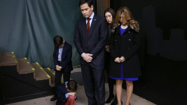 Marco Rubio and his family pray during the opening of a caucus site.