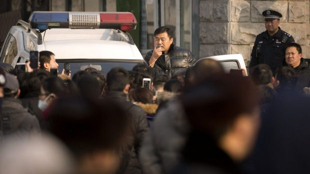 An official uses a loudspeaker on a Chinese police vehicle to speak to depositors from Ezubao outside the State Bureau ...