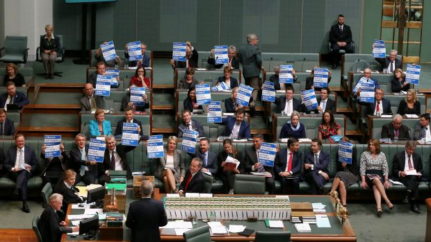 Labor MPs hold up signs on school funding in question time on Tuesday.
