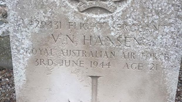 Flowers are laid at Vernon Hansen's grave, yet his family may have no idea he is buried in France.