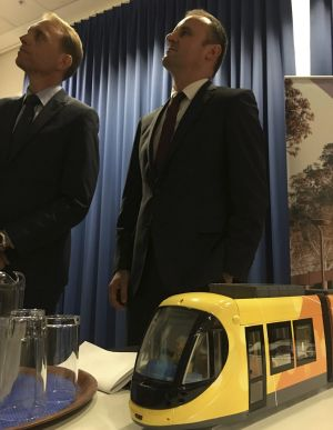 Simon Corbell, left, and Andrew Barr announcing the winning bidder for the Canberra tram, with a model of the ...