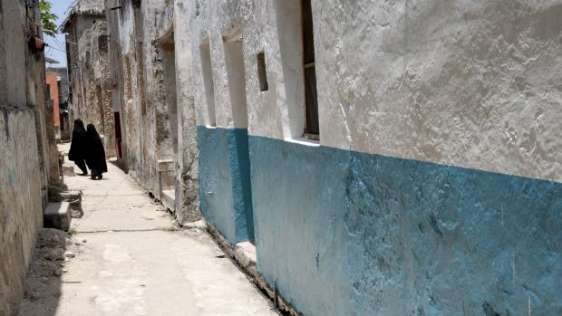 Women walk down a narrow alley of the Old Town on Lamu Island, a UNESCO World Heritage Site.
