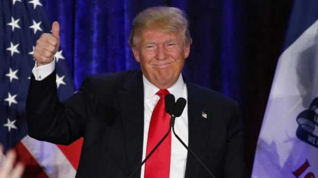 Republican presidential candidate Donald Trump waves after speaking at his caucus night rally in Iowa.