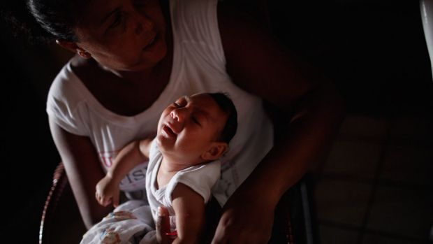 Alice Vitoria Gomes Bezerra, three-months-old, who has microcephaly, is held by her mother Nadja Cristina Gomes Bezerra ...