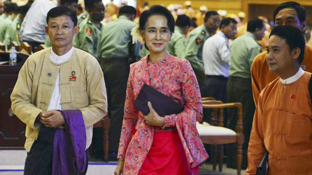 Aung San Suu Kyi, centre, joins National League for Democracy MPs in parliament on Monday.