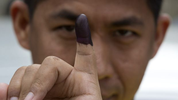 A man shows his finger marked with ink indicating he had voted in November's historic Myanmar election.